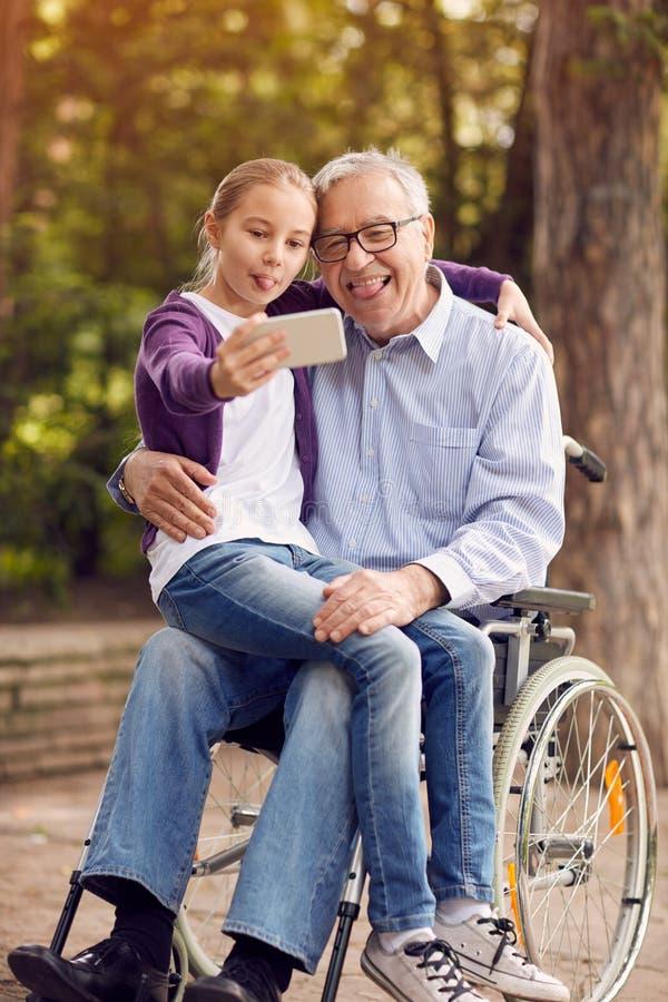 使用电话的滑稽的孙女为与她的残疾油脂的selfie 免版税图库摄影