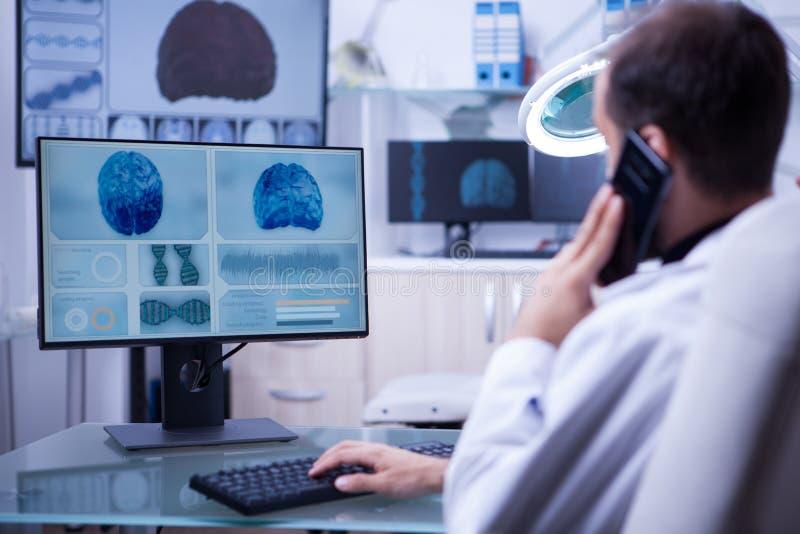 使用电话的男性医生,当工作在计算机键入时 库存照片