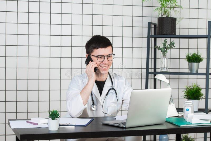 使用电话的男性医生,当研究计算机在桌在诊所时 免版税图库摄影