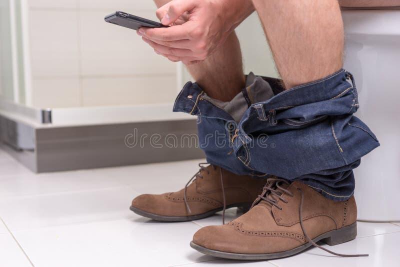 使用电话的男性,当坐马桶时 免版税库存图片