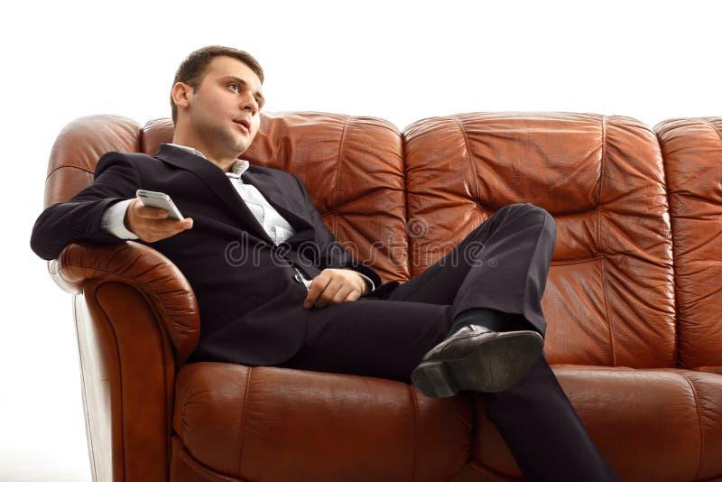 使用电话的疲乏的商人坐沙发 免版税库存图片