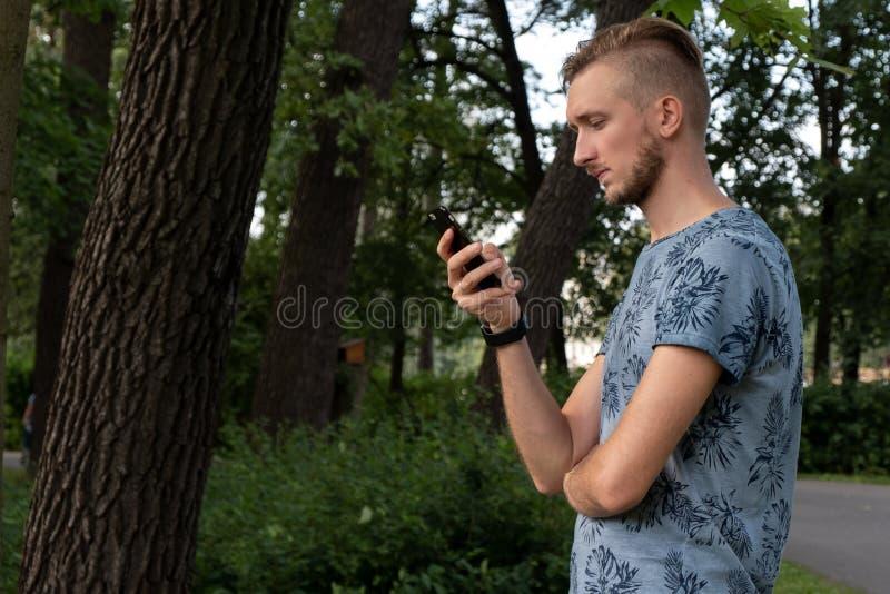 使用电话的英俊的人 有胡子的人文字sms,便衣,蓝色衬衣,俏丽的面孔,行家,可爱,男性在 库存照片