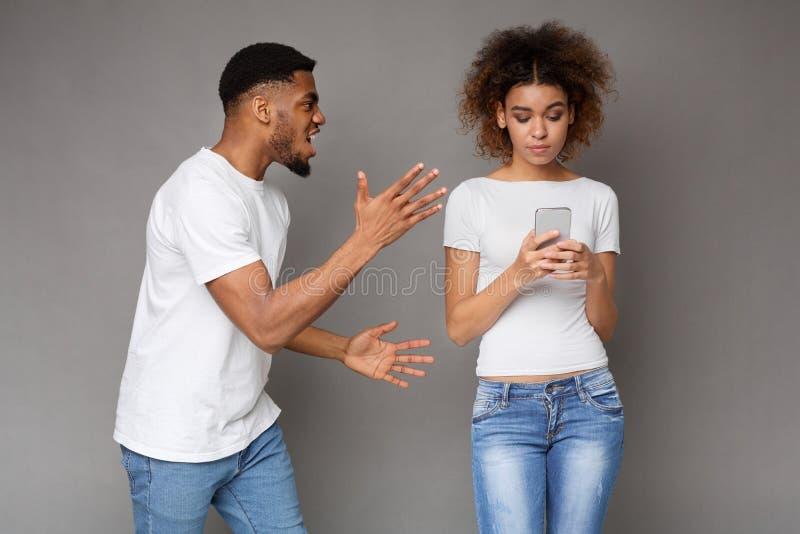 使用电话的黑人妇女,男朋友尖叫对她 库存图片