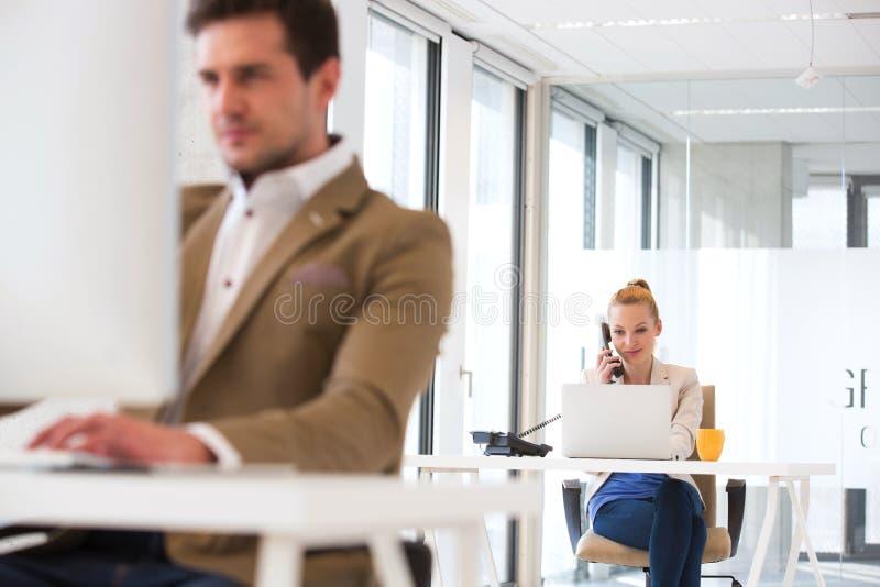 使用电话的年轻商人有前景的男性同事的在办公室 免版税库存图片