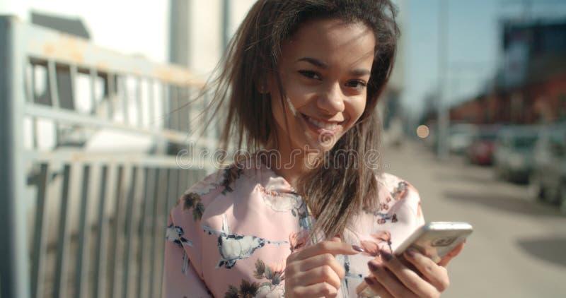 使用电话的年轻非裔美国人的妇女画象,户外 免版税库存图片