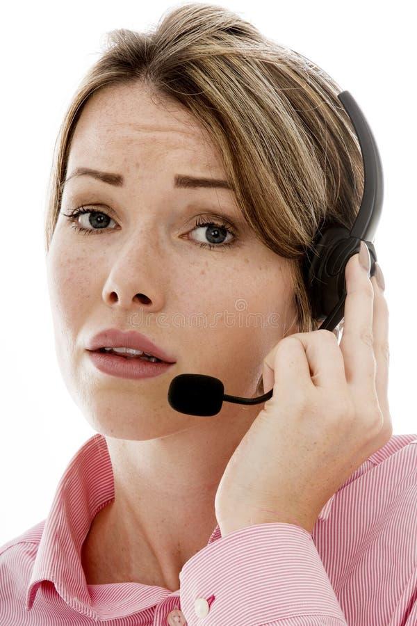 使用电话耳机的可爱的年轻女商人 免版税库存照片