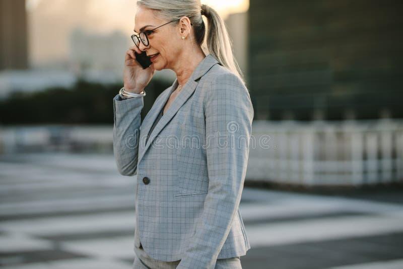 使用电话,在途中的成熟女实业家回家 库存图片