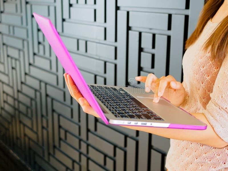 使用白人妇女年轻人,背景计算机图象相当查出膝上型计算机 库存照片