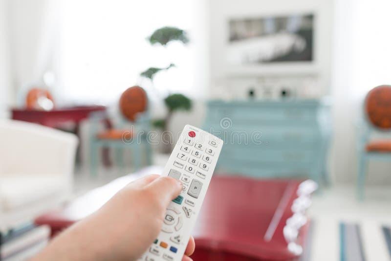 使用白色遥控 编程按在电视键盘的开关或按钮 明亮的客厅 早晨欧洲人家 免版税库存图片