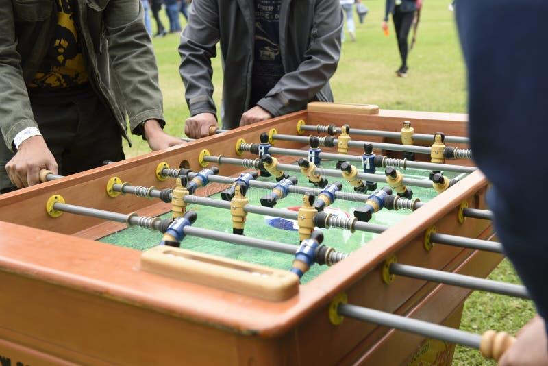 使用的人们享受Foosball表足球赛休闲休闲 免版税库存图片