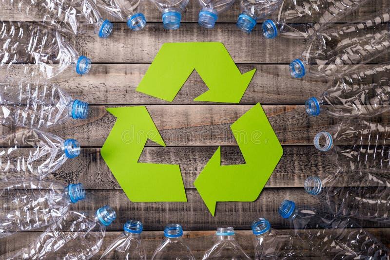 使用的塑料瓶框架有回收的标志在木背景 r 免版税库存照片