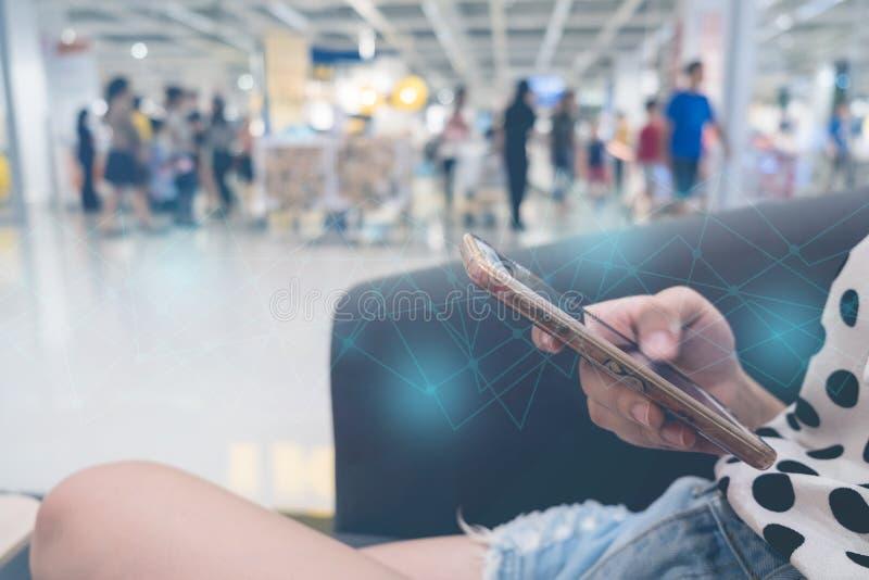 使用的手机的妇女在沙发,蓝线在前面,企业技术连接 库存图片
