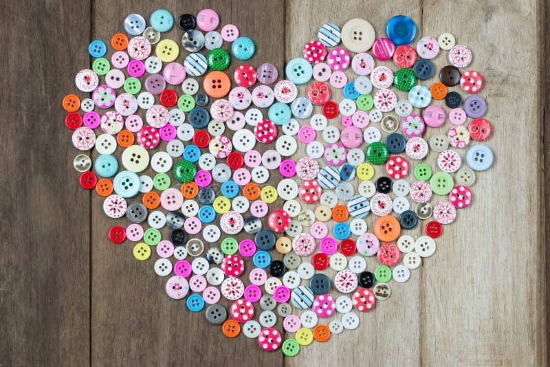 使用的按钮的汇集在心脏形状的在木背景 库存图片