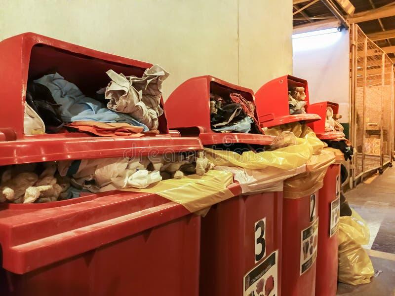 使用的旧布和手套棉花沾染与在红色垃圾桶排序的油在工厂,充分的红色垃圾容器 免版税图库摄影