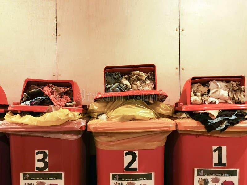 使用的旧布和手套棉花沾染与在红色垃圾桶排序的油在工厂,充分的红色垃圾容器 免版税库存图片