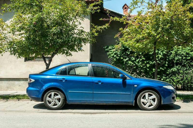 使用的蓝色马自达6汽车在街道上停放了在城市 图库摄影