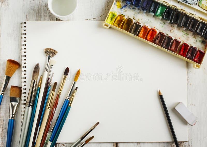使用的水彩绘具箱、水彩纸和画笔 库存图片