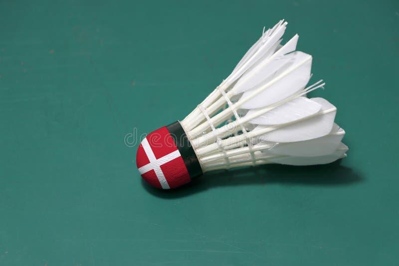 使用的shuttlecock和在头绘与丹麦旗子在羽毛球场绿色地板投入了水平  免版税库存图片