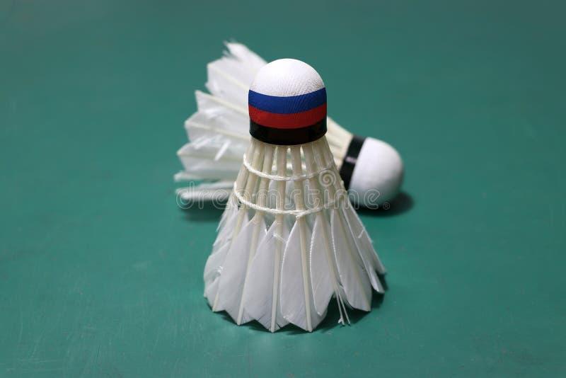 使用的shuttlecock和在头绘与俄罗斯旗子在绿色地板投入了垂直和聚焦shuttlecock投入水平  免版税库存图片
