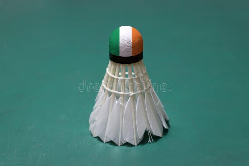 使用的shuttlecock和在头绘与爱尔兰旗子在羽毛球场绿色地板投入了垂直  免版税库存图片