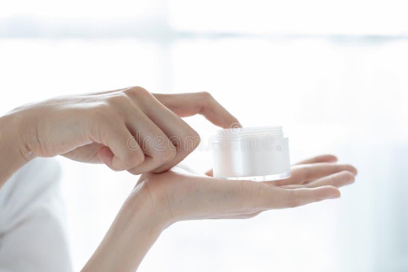 使用皮肤护理产品、润肤霜或者化妆水的一个美女亚洲人照料她的干燥脸色 润湿的奶油  免版税图库摄影