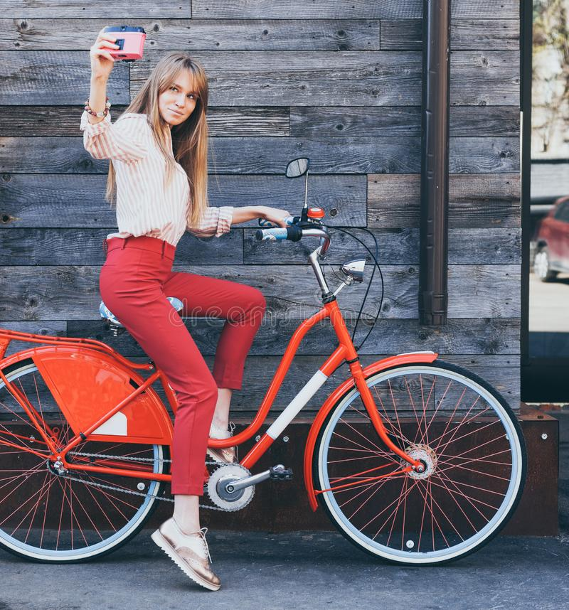 使用相当微笑的少妇采取在桃红色葡萄酒照相机的自画象与在老木板条背景的减速火箭的自行车 免版税库存照片