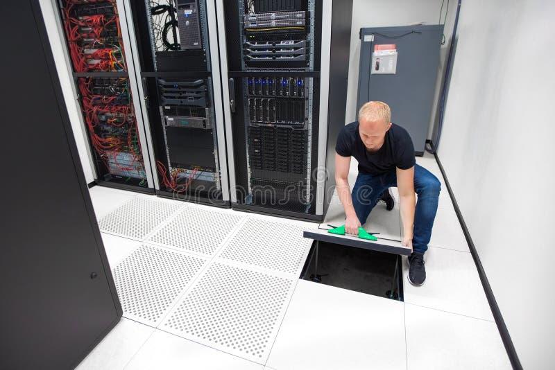 使用真空吸杯的技术员举的地垫在Datac 免版税库存照片
