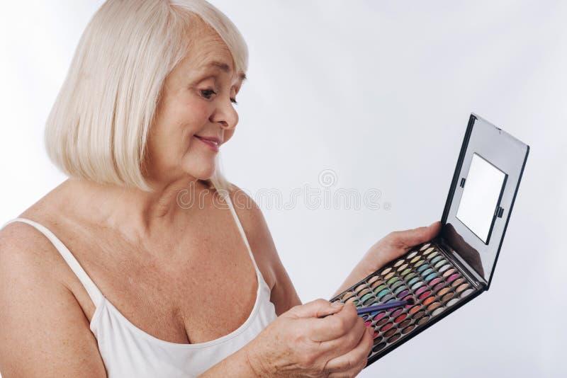 使用眼影膏调色板的快乐的好妇女 库存图片