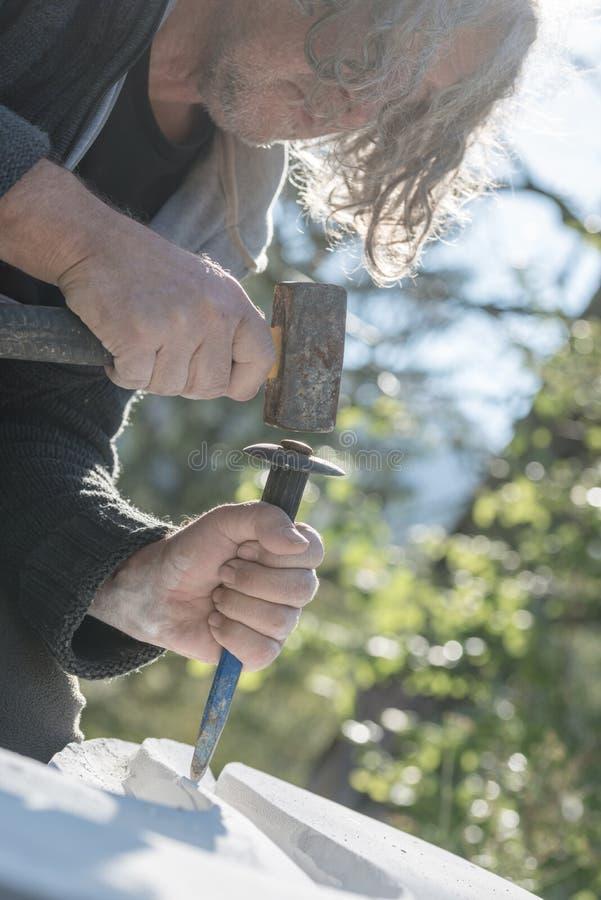 使用短槌和凿子的一位资深艺术家的特写镜头雕刻在石头 免版税库存照片