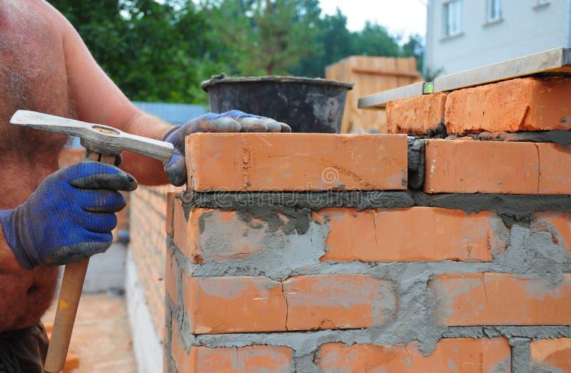使用砌锤子的瓦工修造新的红砖Wal 免版税库存图片