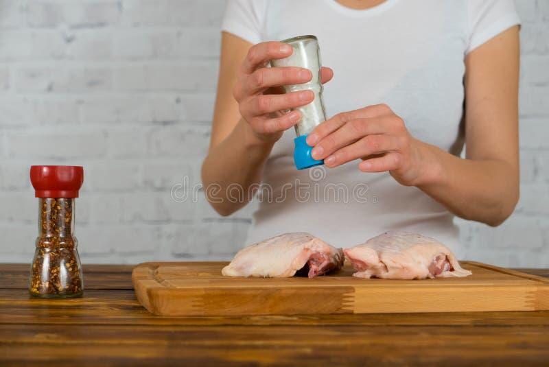 使用研磨机,妇女盐溶鸡 库存照片