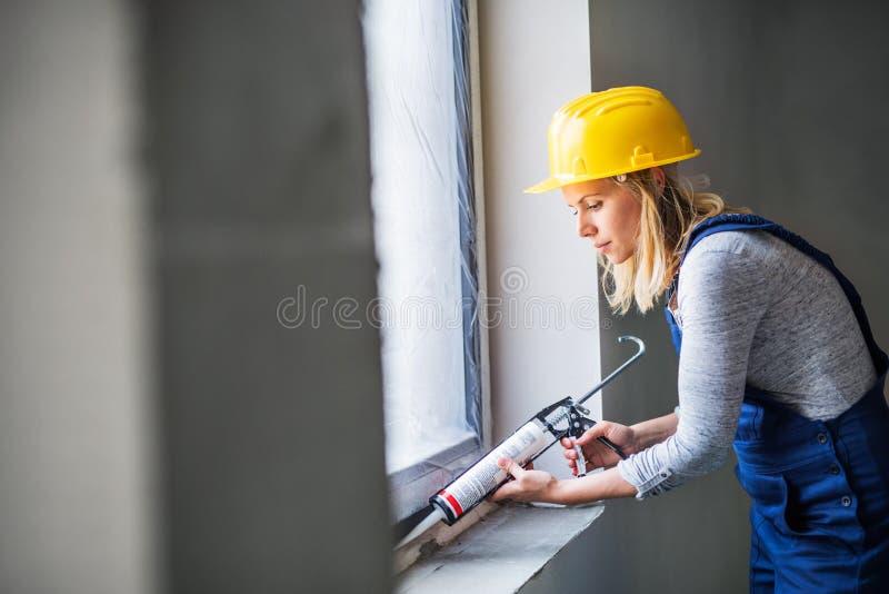 使用硅树脂在建造场所的少妇工作者密封胶枪 库存照片