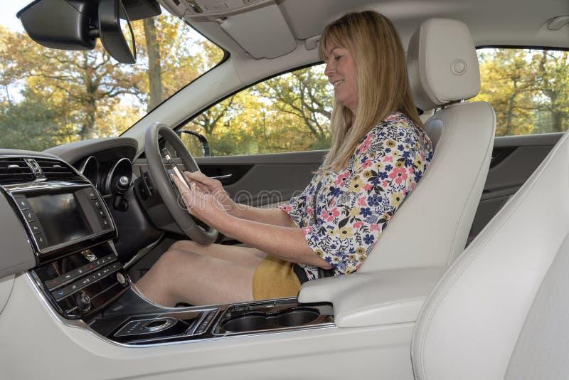 使用移动电话的女性驾驶人从汽车里边 免版税图库摄影