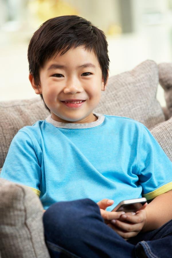 使用移动电话的新中国男孩 免版税库存照片