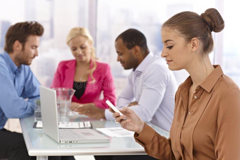 使用移动电话的新女实业家在会议上 免版税图库摄影