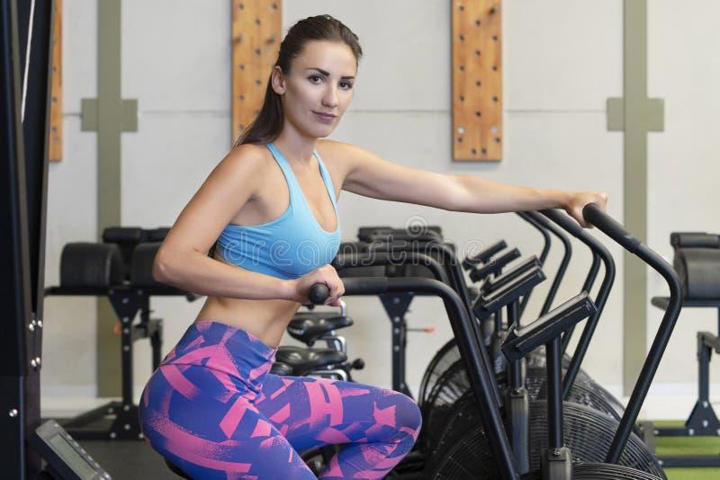 使用空气锻炼自行车的适合的年轻白种人妇女在健身房或健身演播室 库存照片