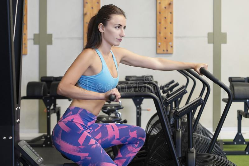 使用空气锻炼自行车的适合的年轻白种人妇女在健身房或健身演播室 库存图片
