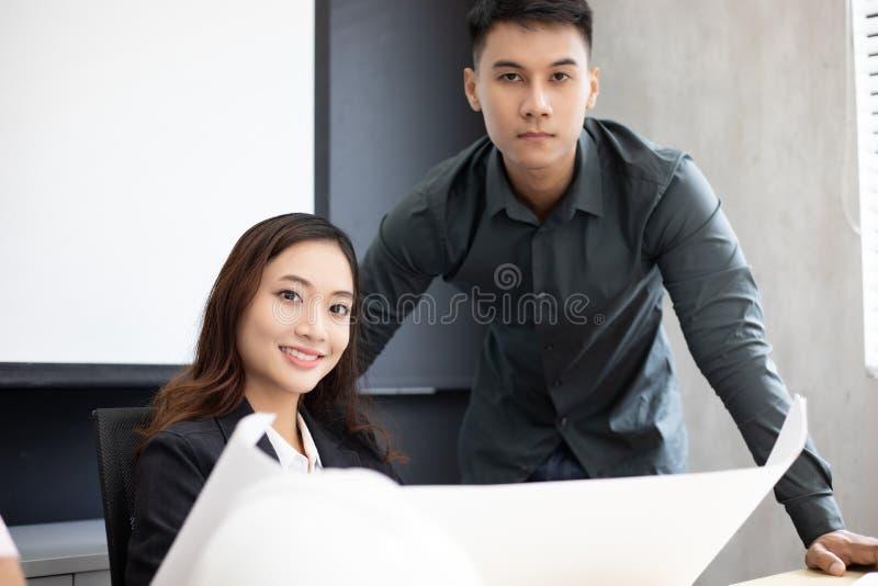 使用笔记本的商人和工程师小组商务伙伴的谈论文件和想法在见面和女商人 库存图片