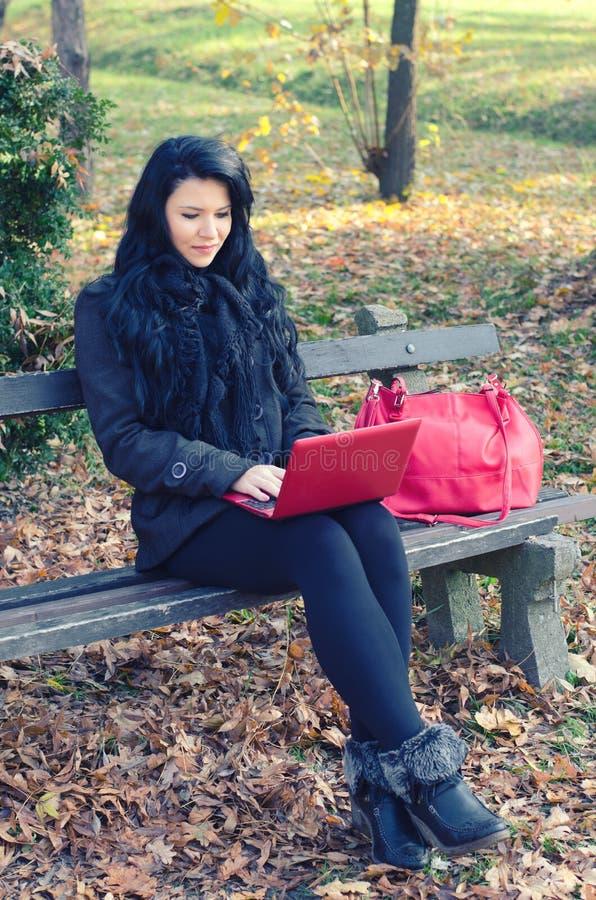 使用笔记本的美丽的愉快的女孩,当坐在秋天公园时 免版税库存图片