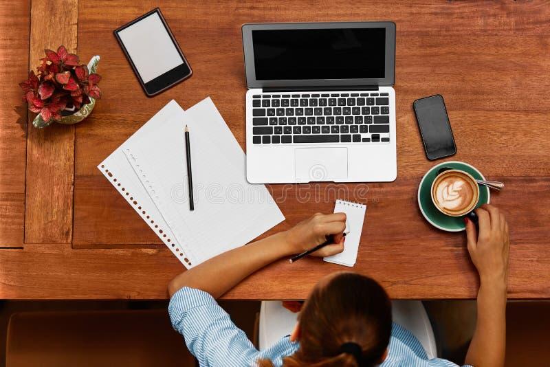 使用笔记本计算机的妇女,采取笔记在咖啡馆 工作 免版税库存照片