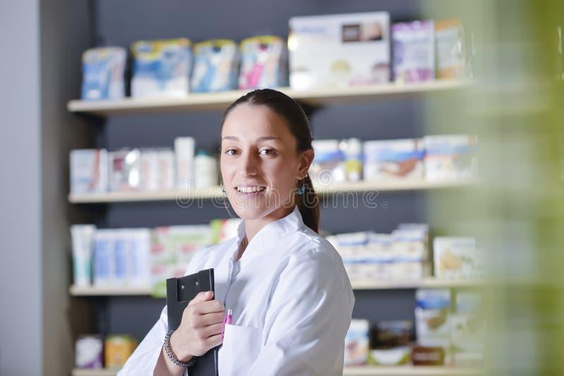 使用笔记薄的美丽的药剂师在药房 免版税库存照片