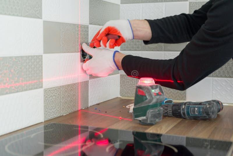 使用红外激光水平的电工安装电子出口 整修和建筑在厨房里 库存照片