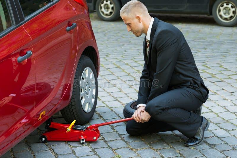使用红色水力地板起重器的人为汽车修理 库存照片