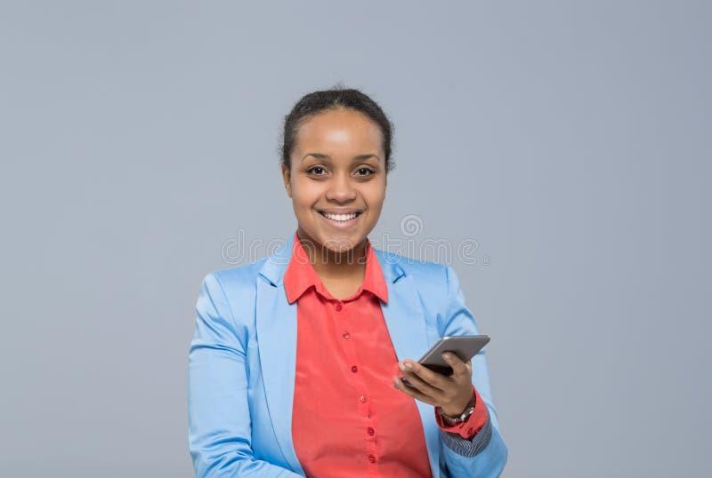 使用细胞聪明的电话非裔美国人的女孩愉快的微笑女实业家的年轻女商人 库存图片
