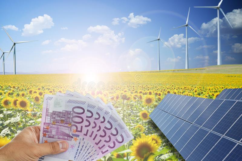 使用绿色能量的攒钱从光致电压的太阳电池板和风轮机 库存照片