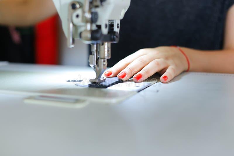 使用缝纫机的裁缝缝合的传送带 免版税库存照片