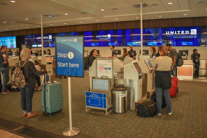 使用美联航自已服务报到的人们在奥兰多国际机场 免版税库存照片