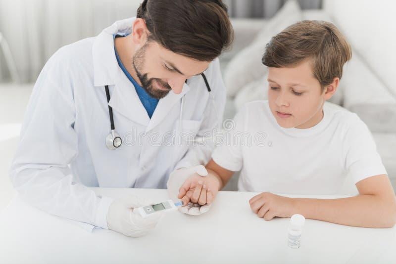 使用翻路机,医生采取从男孩的血液有手指的 男孩刚烈地忍受做法 库存图片