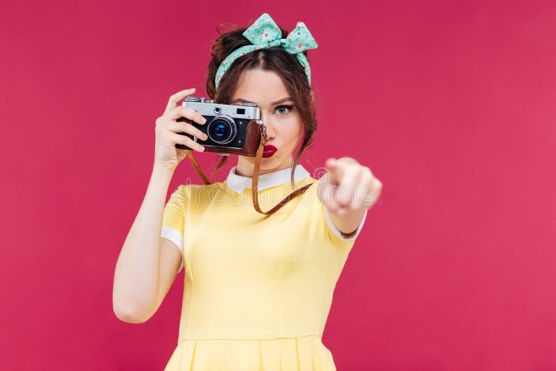 使用老照相机的严肃的逗人喜爱的妇女和指向在您 免版税库存照片