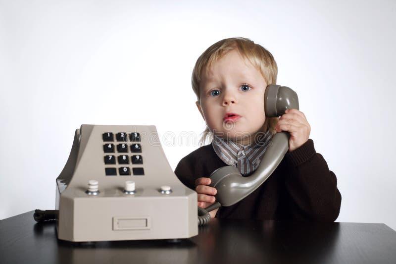 使用老电话的小男孩 图库摄影